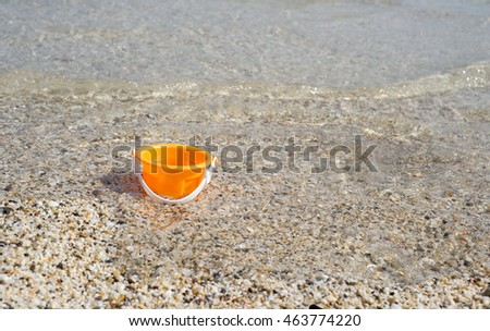 Orange toy bucket  in the seawater