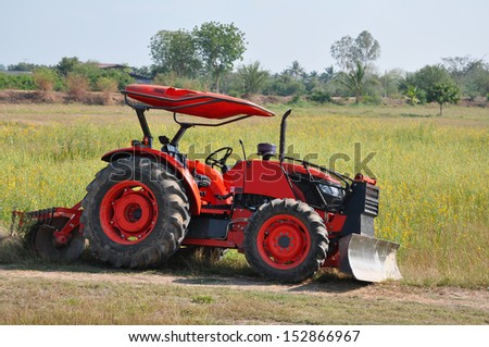 Orange tractor with meadow background, Thailand