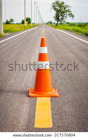 Orange traffic cone on center of country road. It is used for traffic warning and control. - stock photo