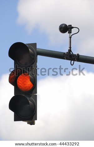 Orange traffic light against cloudy sky. - stock photo