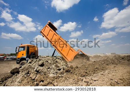 Orange truck tipping dirt on the construction site, blue sky with white clouds in background - stock photo