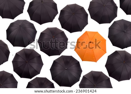 Orange umbrella amongst black umbrellas viewed from above isolated in white - stock photo