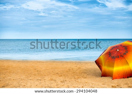 Orange umbrella on golden sand beach in a sunny day, blue sea in background