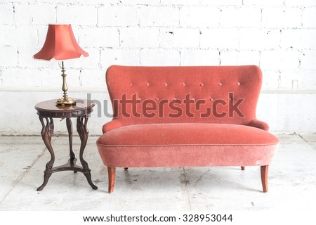 Orange vintage sofa and lamp on white wall.
