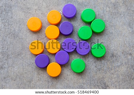 Orange, violet and green plastic bottle caps, top view