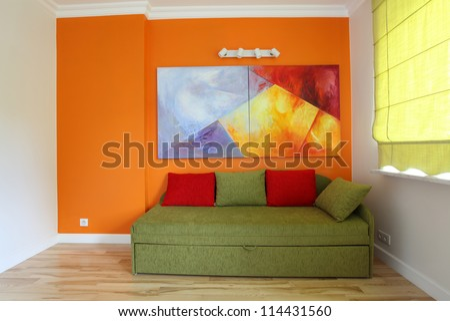 Orange wall and green sofa in teenage room - stock photo
