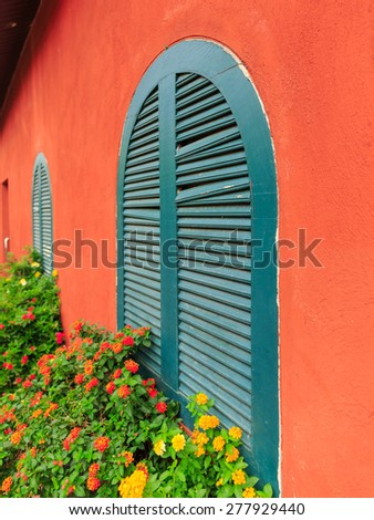 orange wall and green wood windows with colorful flowers - stock photo