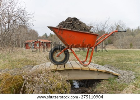 Orange wheel barrow full of mud standing on a small bridge