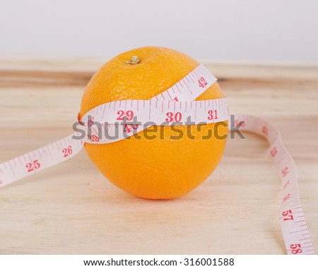 Orange with centimeter on wood background, lose weight concept  - stock photo