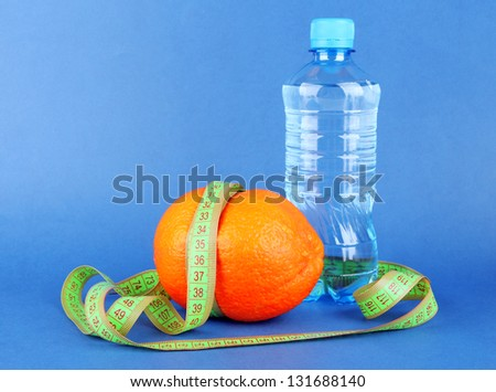 Orange with measuring tape, bottle of water, on color background - stock photo