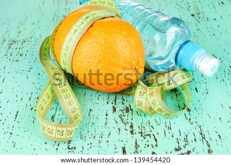 Orange with measuring tape, bottle of water, on  color wooden background - stock photo