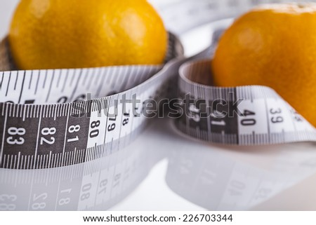 Orange with measuring tape Diet food concept. Weight loss,