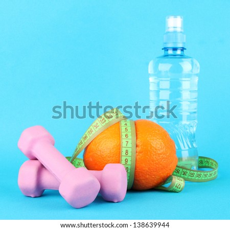 Orange with measuring tape, dumbbells and bottle of water, on color background - stock photo