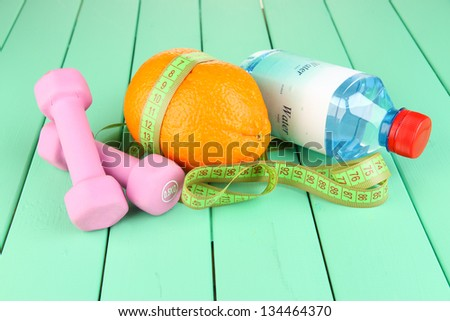 Orange with measuring tape, dumbbells and bottle of water, on color wooden background - stock photo
