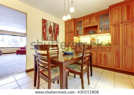 Orange wood kitchen cabinets with dining room table with apples. - stock photo