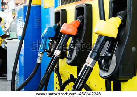Orange,Yellow and Blue fuel nozzles in the fuel dispenser in the Petrol Station - stock photo