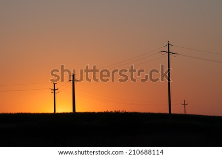 Orange, yellow sunset and four electric pylons