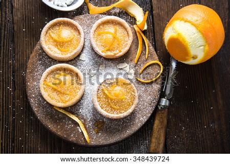 Orange zesty homemade artisan tarts, on wooden board - stock photo