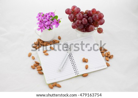 Oranges, almonds, books and flowers on a white background.