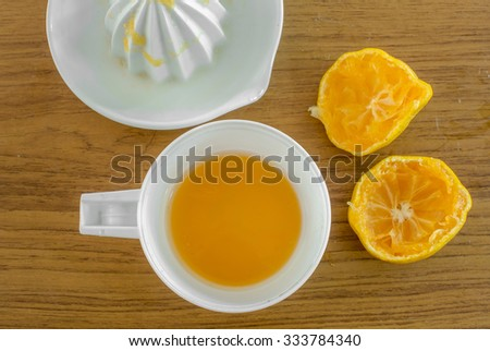 Oranges and a squeezer on wooden table - stock photo