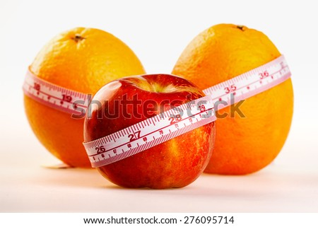 Oranges and apple with tailor's ruler. Fruit healthy vitamin diet helps to lose weight. - stock photo