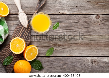 Oranges and juice glass on wooden table. Top view with copy space - stock photo