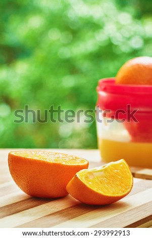 Oranges and juicer on the wooden cutting board on green blurred background