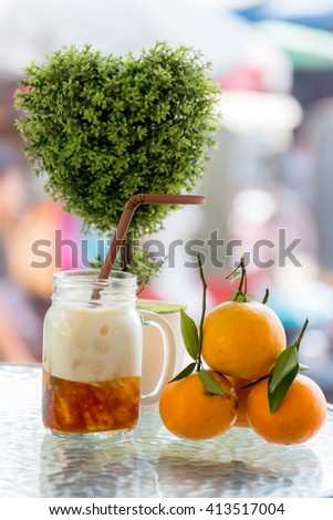 oranges and soft drink on table glass, on blurry background.