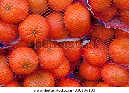 Oranges at the food market in red mesh bags - stock photo