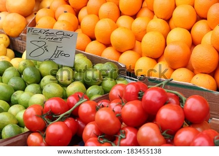 Oranges, limes and tomatoes at a marketplace in United Kingdom. Farmers market. - stock photo