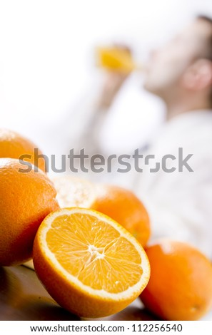 Oranges on table, man drinking orange juice - stock photo