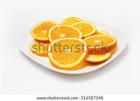 Oranges on white plate. Shallow depth of field. Selective focus. - stock photo