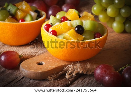 Oranges stuffed with fresh fruit salad close-up on the table. horizontal  - stock photo