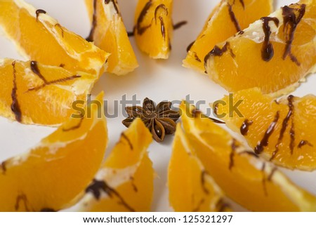 Oranges with anise and chocolate on the plate