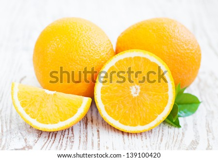 Oranges with leaves on a wooden background