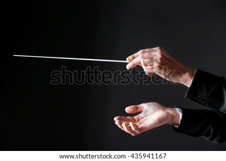 Orchestra conductor hands on dark background