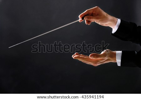Orchestra conductor hands on dark background - stock photo