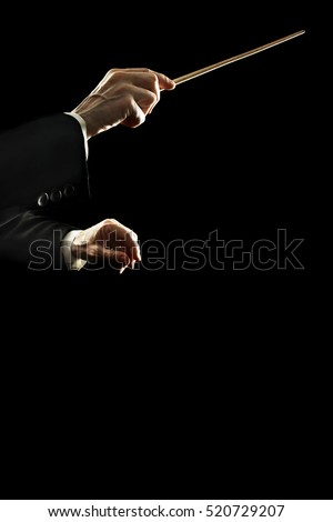 Orchestra conductor music conducting. Conductors hands with baton stick isolated on black background