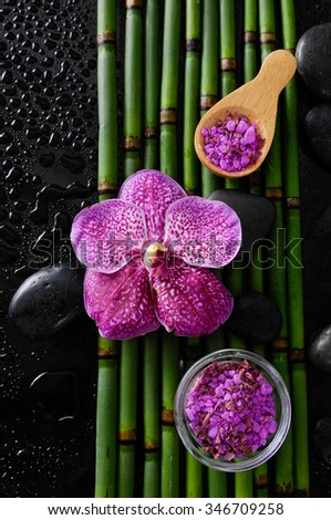 orchid and bamboo grove, salt in bowl,spoon on wet black background   - stock photo