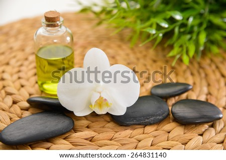 Orchid and stones ,oil ,green plant on Wicker place mat  - stock photo