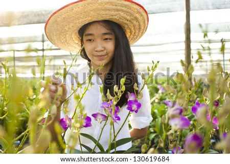 orchid and woman, Young Asian girl wearing weave hat in orchid farm - stock photo