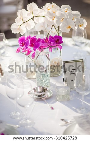 Orchid centerpiece at an outdoor event or wedding reception - stock photo