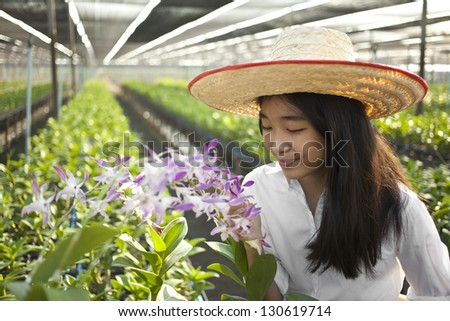 orchid farm owner, Young Asian girl wearing weave hat pose in orchid farm - stock photo