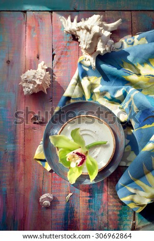 Orchid flower and seashells, on brightly colored wooden background. Holiday by tropical sea concept. - stock photo