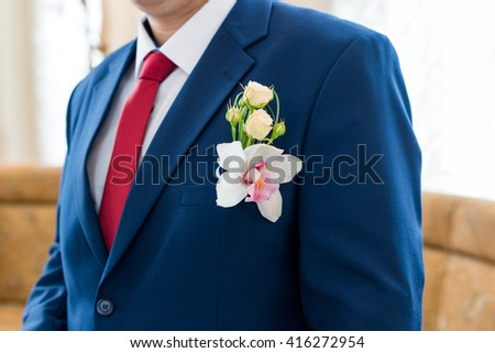 Orchid flower in the buttonhole of groom - stock photo