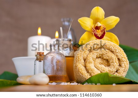 Orchid flower, towel, aroma oils, zen stones, over wooden surface - stock photo