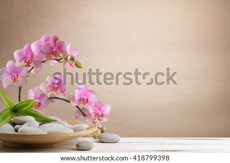 Orchid flowers and spa stones on wooden plate - stock photo