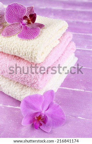 Orchid flowers and towels on color wooden background - stock photo