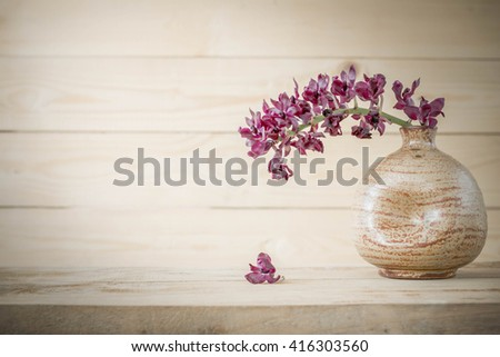 Orchid in a Vase on wood , vintage style. - stock photo