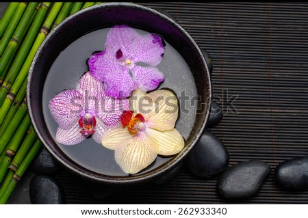 orchid in bowl with thin bamboo grove and stones, candle on bamboo mat  - stock photo